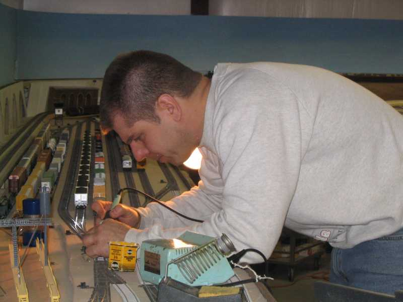 Scott Kurzawski uses his soldering iron to repair a turnout leading to Conroe Yard on the layout of APN