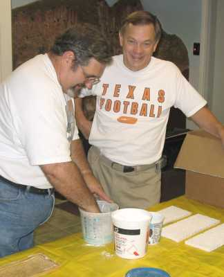 Mike Kremheller supervises as Charlie Richmond mixes Hydrocal to make castings at APN