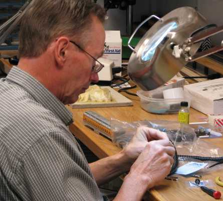 Roger Macauley soldering a DIN plug to a cab cable on the workbench at APN